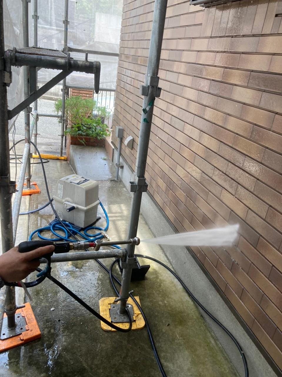 生駒市の屋根塗装現場で外壁の洗浄作業