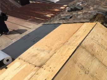 屋根に防水紙を張っていく様子