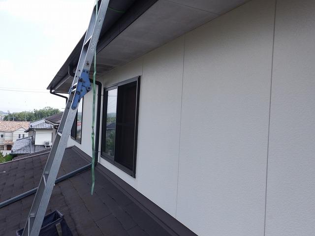 下屋根から梯子を掛けて大屋根に上がるところ