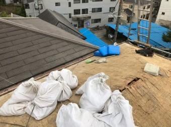 屋根の上に大量の土のう袋