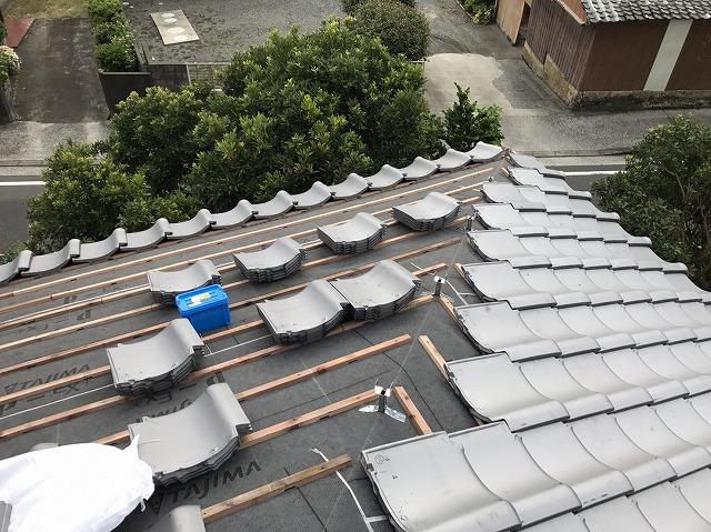 屋根に瓦を葺いていく様子